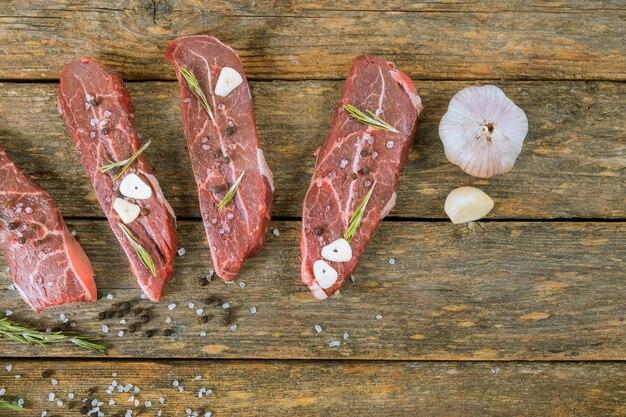 Bife de carne crua em uma mesa de madeira.