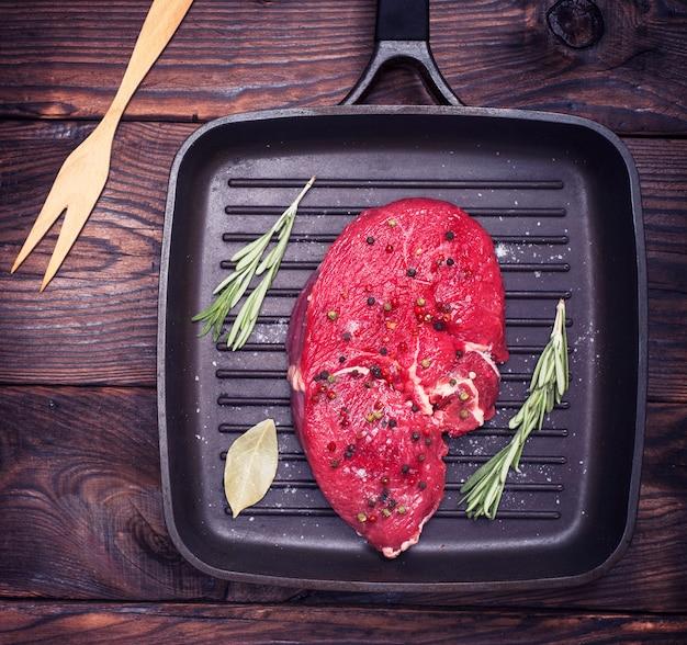 Bife de carne crua em uma panela de quart preto
