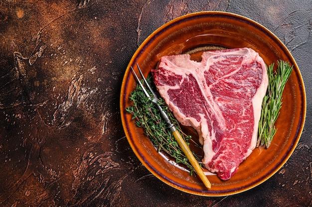 Bife de carne crua t-bone com ervas em um prato. fundo escuro. vista do topo. copie o espaço.