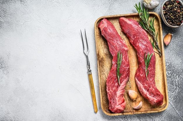 Bife de carne de bovino angus preto em mármore cru. fundo branco. vista do topo. copie o espaço.