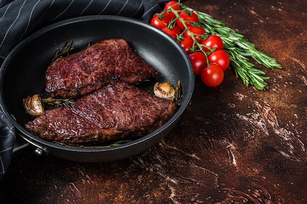 Bife de carne de denver grelhado em uma panela com alecrim. fundo escuro. vista do topo. copie o espaço.