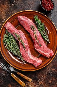 Bife de carne de flanco cru em um prato. fundo escuro. vista do topo.