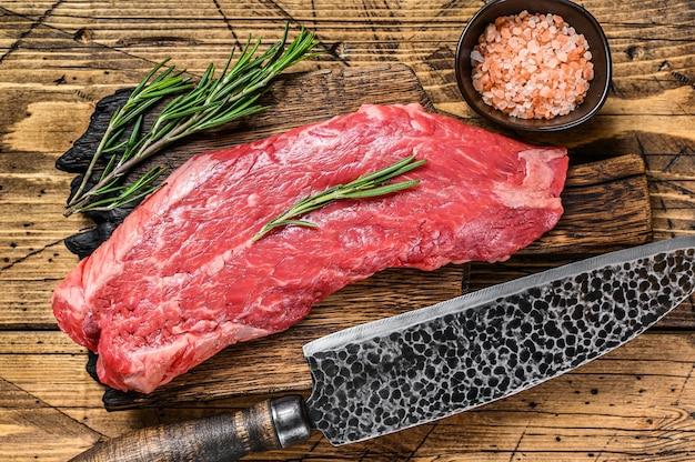 Bife de carne de flanco crua em uma placa de corte com faca. fundo de madeira. vista do topo.