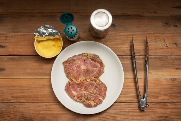 Bife de carne de porco cru de marinada em chapa branca ao lado com pimenta