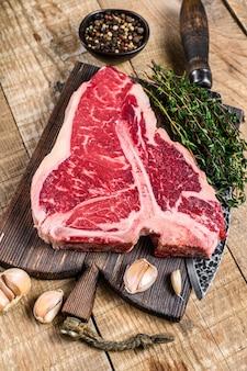 Bife de carne de porterhouse ou t-bone crua com ervas em uma tábua de madeira. fundo de madeira. vista do topo.