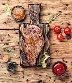 Bife de carne em um fundo de madeira