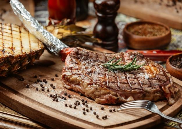 Bife de carne em um prato de madeira com pimenta preta e alecrim.