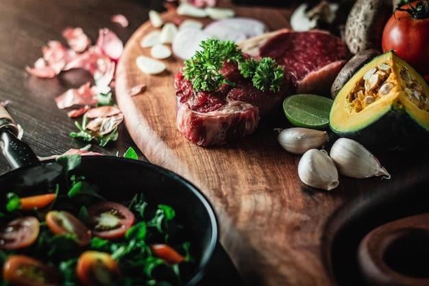 Bife de carne em uma placa de corte com uma faca e ingredientes