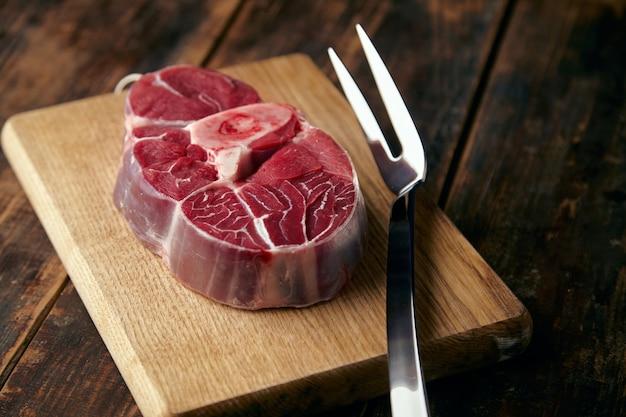 Bife de carne fresca com osso em prato de madeira com garfo grande