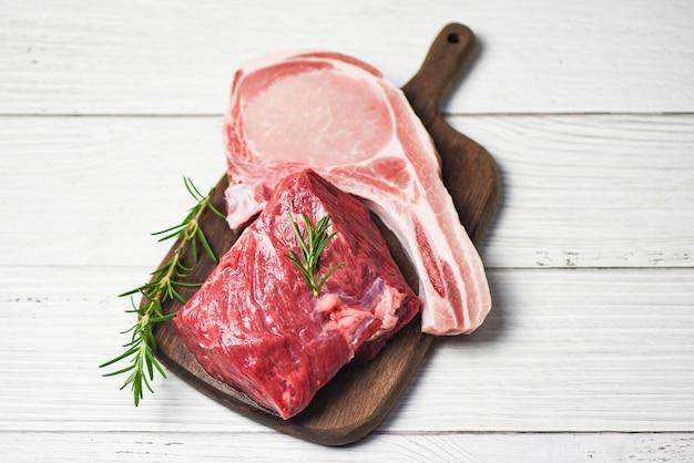 Bife de carne fresca cortada e costeletas de porco no fundo da tábua de madeira - bife cru com alecrim