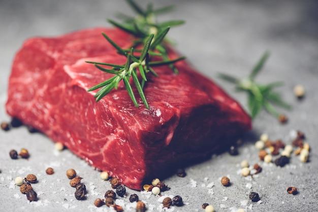 Bife de carne fresca cortada em fundo preto - bife cru com ervas e especiarias e alecrim no prato