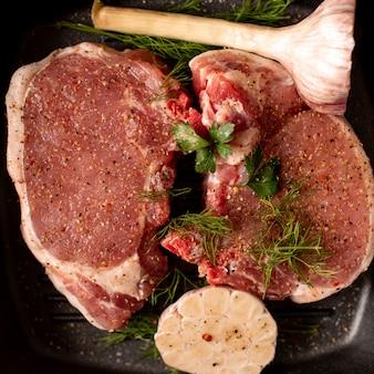 Bife de carne fresca crua na panela de ferro grill, tempero e garfo de carne na madeira
