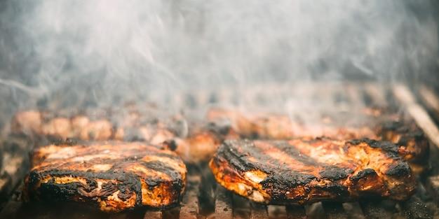 Bife de carne frito em uma gradinha com fumaça e fogo