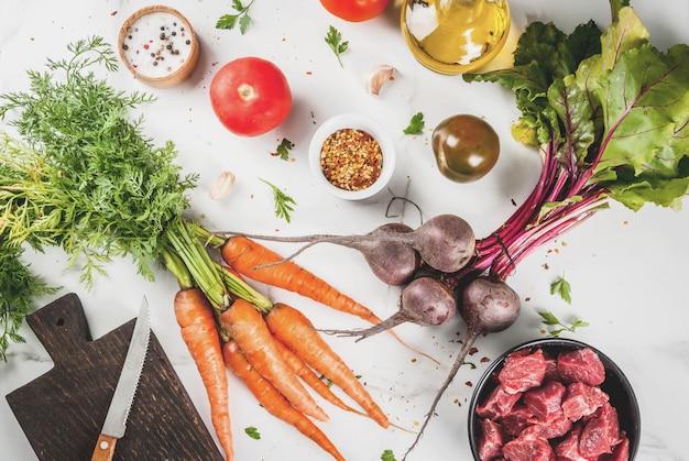 Bife de carne. goulash picado cru fresco, cubos de carne em uma tigela. especiarias (sal, pimenta), tomate, alho, cebola. em uma mesa de mármore branco, com um garfo para carne e uma faca. vista do topo