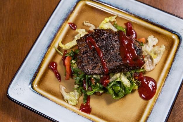 Bife de carne grande com legumes e molhos em placa quadrada na mesa de madeira em restaurante de luxo