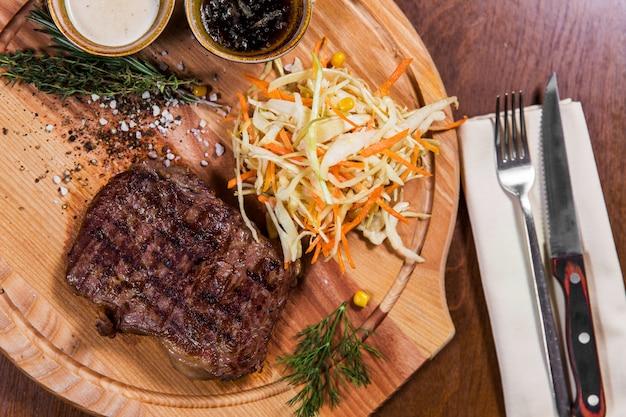 Bife de carne grande com legumes e molhos, faca e garfo na mesa de madeira em restaurante de luxo
