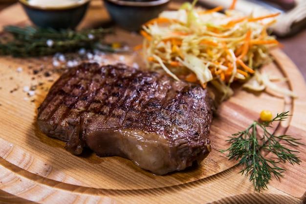 Bife de carne grande com legumes, verdura e molhos na mesa de madeira no restaurante de luxo