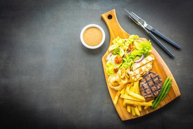 Bife de carne grelhada com molho de batatas fritas e legumes frescos