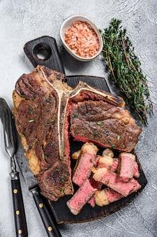 Bife de carne grelhada em fatias de t-bone em uma tábua de madeira. fundo branco. vista do topo.