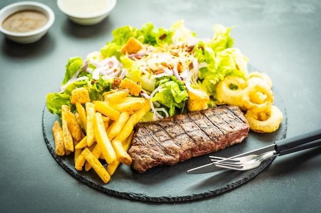 Bife de carne grelhado com batatas fritas anel de cebola com molho e legumes frescos