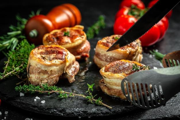 Bife de carne mal passado grelhado, magro e saudável. bife de filé mignon coberto com bacon. fundo de receita de comida. fechar-se.