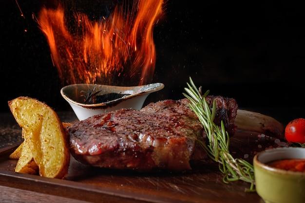 Bife de carne no fogo, numa tábua de madeira, com batatas e molho, sobre fundo preto