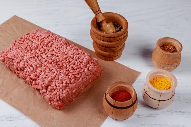 Bife de carne picada crua com várias especiarias em uma placa de madeira