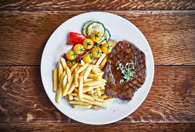 Bife de churrasco com batata frita servido em mesa de madeira