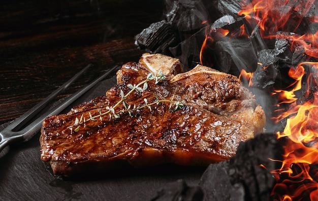 Bife de churrasco em uma placa de ardósia preta com garfo de carne e grelha de carvão