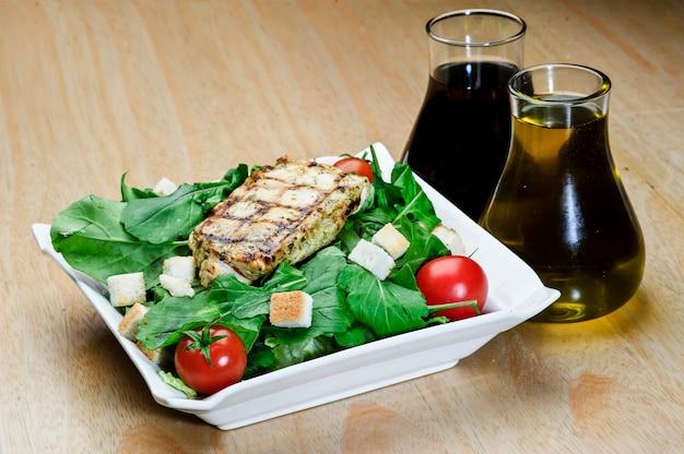 Bife de cordeiro assado com pimenta-do-reino assado com saladas e batatas fritas em prato redondo azul