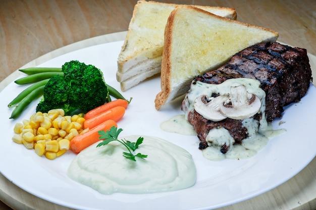 Bife de cordeiro assado com pimenta-do-reino com saladas e batatas fritas em prato redondo azul. fundo de textura de madeira.