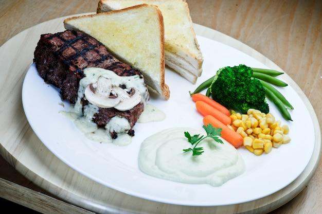 Bife de cordeiro assado pimenta preta com saladas e batatas fritas em um prato redondo azul. fundo de textura de madeira.