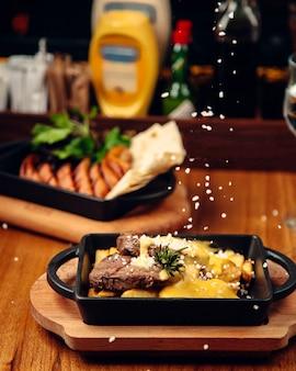 Bife de cordeiro servido com batata frita e queijo derretido