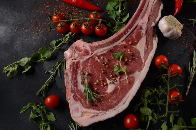 Bife de costela com osso de carne crua fresca no quadro negro com ervas e especiarias
