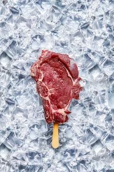 Bife de costela de boi crua com palito de sorvete em pedaços de gelo