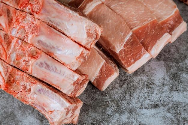Bife de costeleta cru da carne de porco na placa de corte.
