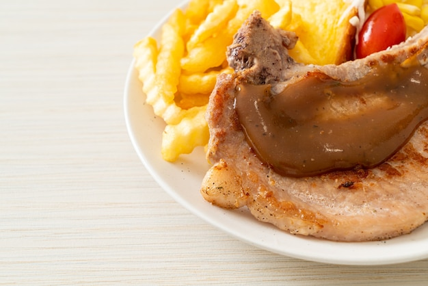Bife de costeleta de porco com batatas fritas e mini salada em prato branco