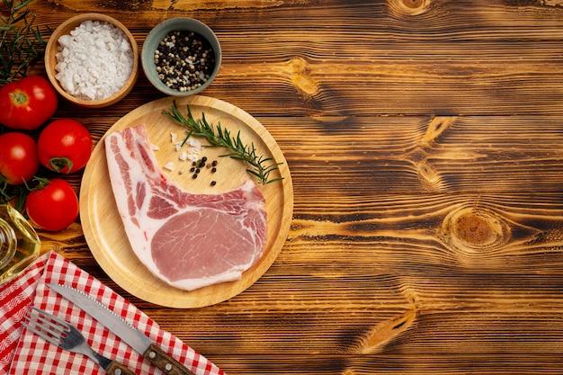 Bife de costeleta de porco crua na superfície de madeira escura.