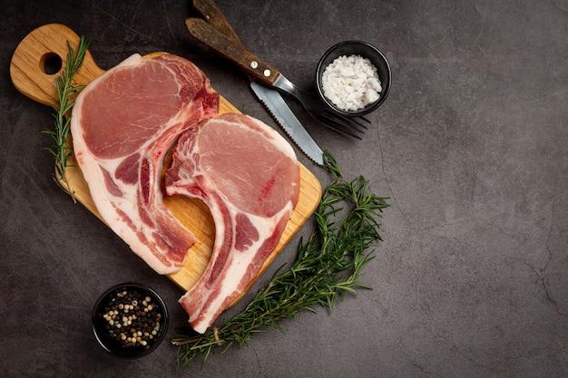 Bife de costeleta de porco crua na superfície escura.