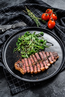 Bife de entrecosto de filé, carne de bovino marmorizada com rúcula.