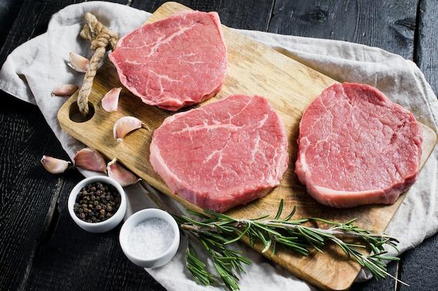 Bife de filé de carne crua em uma tábua de cortar madeira