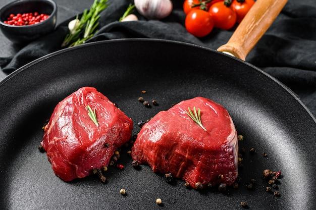 Bife de filé mignon em uma frigideira. lombinho de carne. fundo preto. vista do topo