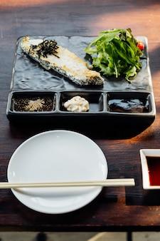 Bife de filete japonês de robalo servido com salada, maionese e molho shoyu.