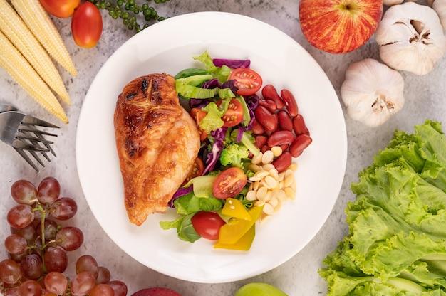 Bife de frango coberto com gergelim branco, ervilhas, tomates, brócolis e abóbora em um prato branco.