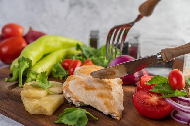 Bife de frango colocado em uma bandeja de madeira.