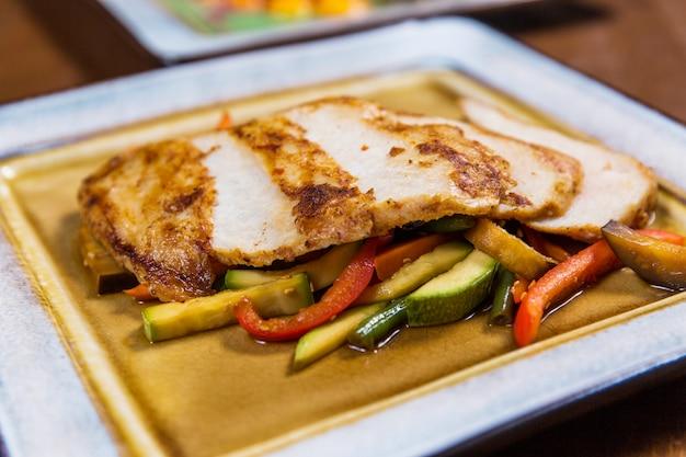 Bife de frango grande com legumes na chapa quadrada na mesa de madeira no restaurante de luxo