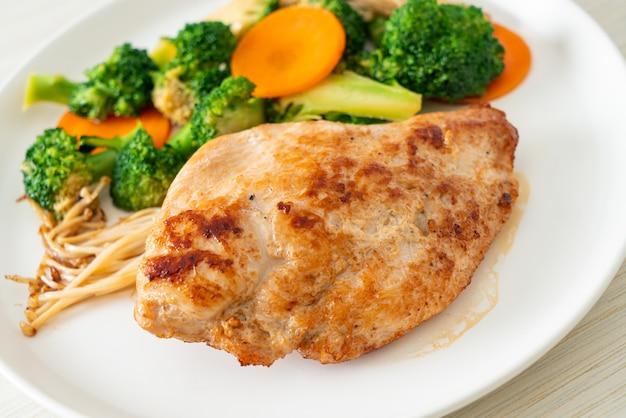 Bife de frango grelhado com vegetais no prato branco