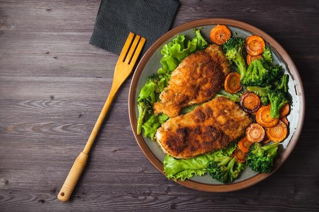 Bife de frango na farinha de rosca com legumes em um prato