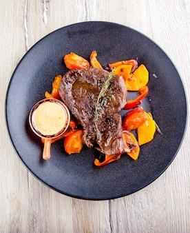 Bife de lombo com mostarda e vegetais grelhados em um prato vista de cima