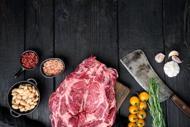 Bife de lombo cru, carne marmorizada com conjunto de pimenta e ervas e faca de cutelo de açougueiro velho, na mesa de madeira preta, vista de cima plana lay